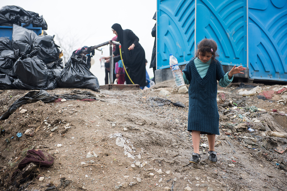 A young girl walks from the portaloos back to her tent, next to a pile of rubbish. Transit camp of Idomeni, Greece. <br /> <br /> Thousands of refugees are stranded in Idomeni unable to cross the border. The facilities are stretched to the limit and the conditions are appalling.
