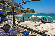Man enjoys his lunch at a seaside restaurant in the Italian resort island of Capri.