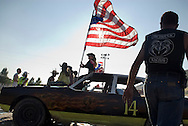 NEWS&GUIDE PHOTO / PRICE CHAMBERS.Rodeo Queen Erin Heffron keeps a firm grip on Old Glory atop the demolition derby car built by Redneck Racing, then auctioned off just before the derby. Dominoes Pizza bought the car for $3,700 and put one of their delivery drivers behind the wheel. All of the proceeds are donated to the Jackson Hole Fire Department.