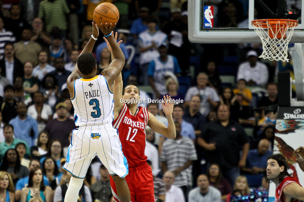 April 6, 2011; New Orleans, LA, USA; New Orleans Hornets point guard Chris Paul (3) shoots over Houston Rockets shooting guard Kevin Martin (12) during the fourth quarter at the New Orleans Arena. The Hornets defeated the Rockets 101-93 and clinched a playoff spot with the victory.   Mandatory Credit: Derick E. Hingle-US PRESSWIRE