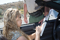 Woman in car signing speeding ticket for policeman