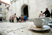 Close up of coffee cups, old town buildings in background. Trogir, Croata