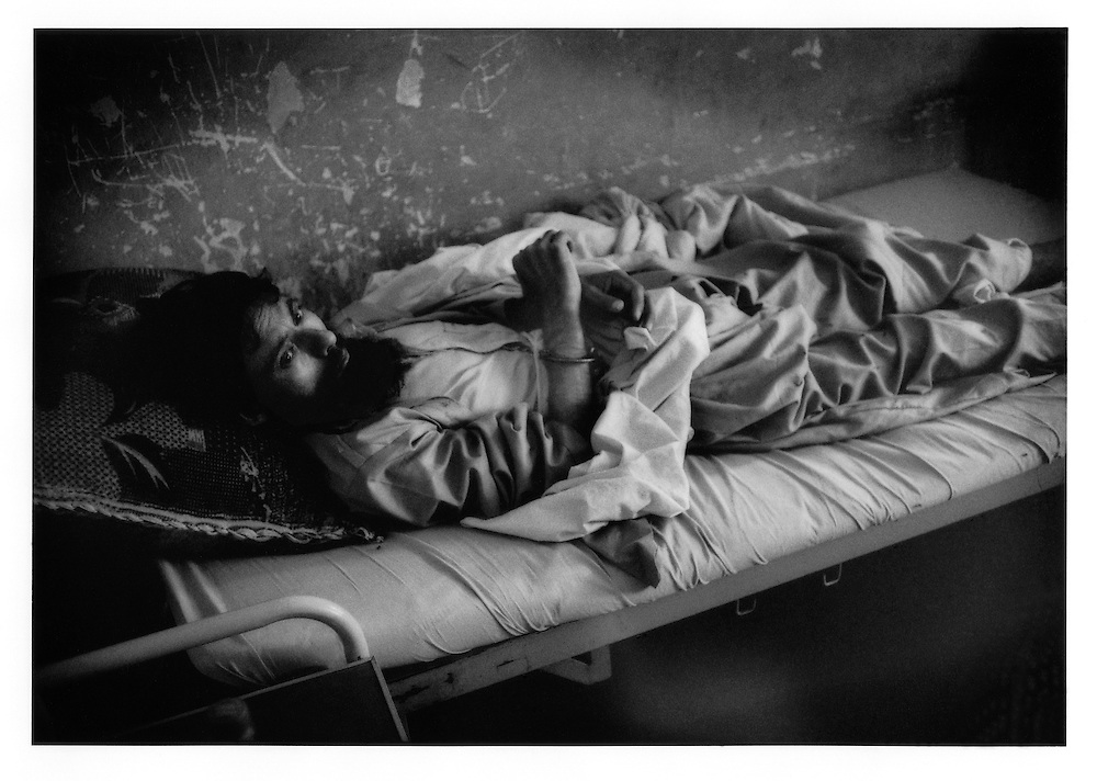 """Pakistani """"patient"""" has been handcuffed by police who what outside the forensic psychology ward Kabul's only gov?t run mental hospital, Psychiatric and Drug Dependency Hospital, Kabul, Afghanistan."""