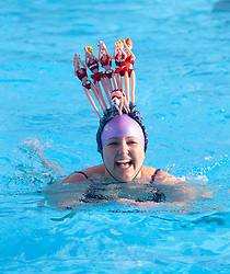 © Licensed to London News Pictures. 24/01/2015. London, UK. Contestant Ella Foote wears a fancy hat made of dolls at the 6th UK Cold Water Swimming Championships at Tooting Bec Lido, south London. Over, 650 swimmers will take the plunge to compete in a variety of chilly races.  Photo credit : Isabel Infantes / LNP