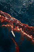 A ship drifts amidst a heavy band of oil spilled in the Gulf of Mexico from the Deepwater Horizon wellhead, May, 2010.