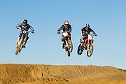 Three motocross Racers in mid-air