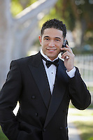 Portrait of man in tuxedo outdoors, using mobile phone