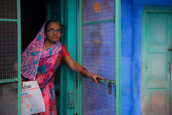 A woman in colorful sari in doorway of her home in the blue city of Jodphur, Jodphur, Rajasthan, India,