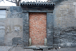 Historic traditional doorway to house in Beijing hutong bricked up prior to demolition in area undergoing redevelopment 2009