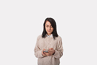 Businesswoman text messaging through smart phone against gray background