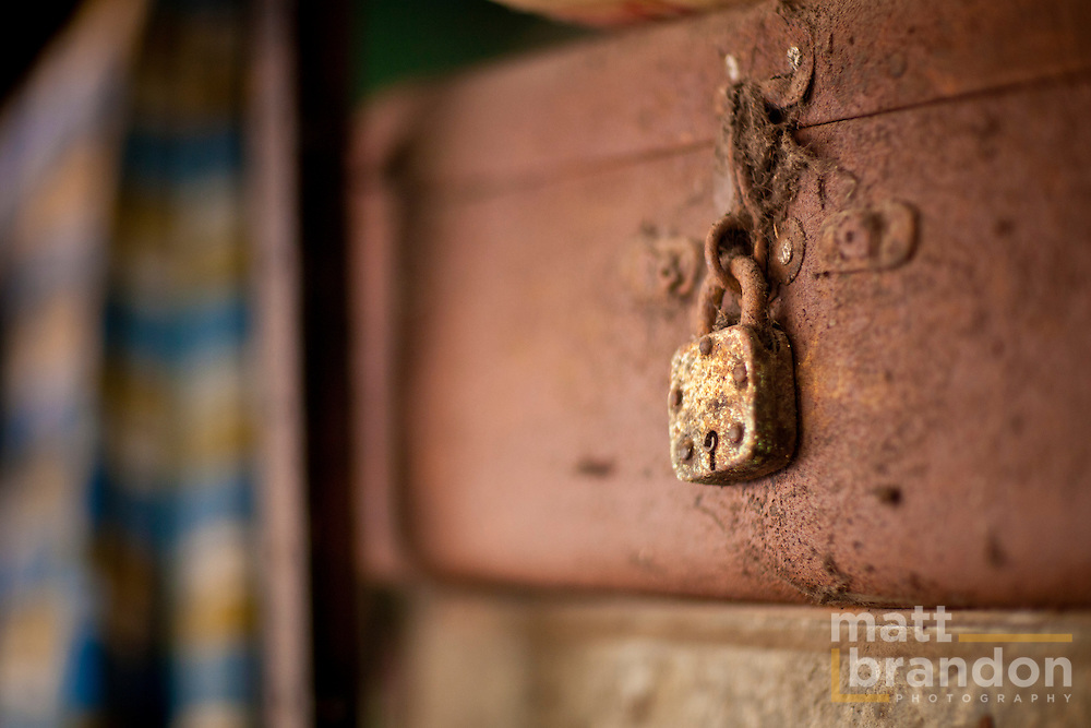 Old, rusty locked luggage is stored on shelves. The men bring with them very little when they move to the city to find work.