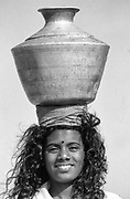 Young woman carrying drinking water collected from a beach side fresh water well at Udappu.<br /> West Coast.
