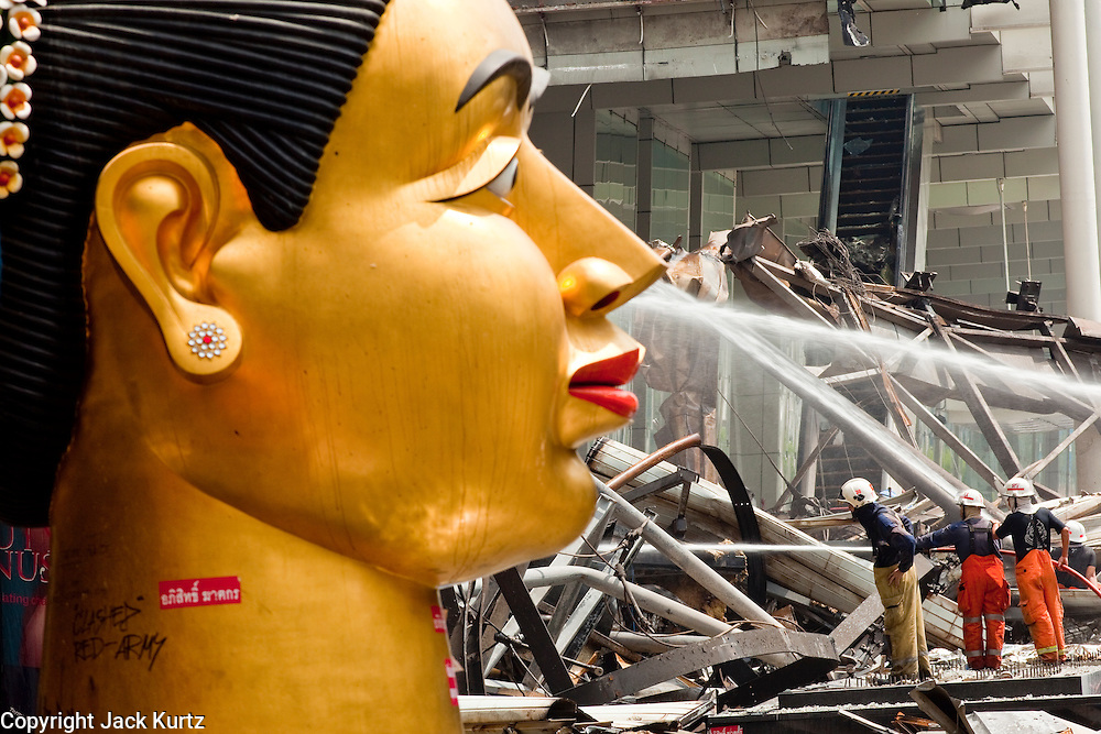 20 MAY 2010 - BANGKOK, THAILAND: A large Buddha head was undamaged in a fire that destroyed the Central World shopping mall in the Ratchaprasong Intersection in Bangkok Thursday. Firefighers are still working to extinguish the blaze. The day after a military crackdown killed at least six people, Thai authorities continued mopping up operations around the site of the Red Shirt rally stage and battle fires set by Red Shirt supporters in the luxury malls around the intersection. Anti government forces set fire to the mall and several other locations across Bangkok after their leaders surrendered to police.  PHOTO BY JACK KURTZ