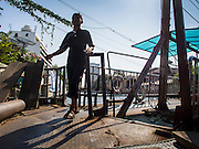 19 JANUARY 2015 - BANGKOK, THAILAND: A passenger gets off the ferry on the Phetchaburi Road side of Khlong Saen Saeb. The small ferry crosses Khlong Saen Saeb throughout the day. It is powered by an diesel engine that uses a system of cables to pull the ferry the 30 feet across the canal. It's used by pedestrians  who need to get across the khlong. The nearest bridge is about ½ mile away.     PHOTO BY JACK KURTZ