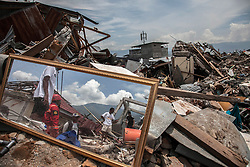 October 4, 2018 - Palu, Central Sulawesi, Indonesia - Villagers search for salvageable items among the ruins of a house devastated after the earthquake and tsunami hit the area on September 28, in Balaroa Village, Central Sulawesi, Indonesia. A total of 1,411 people have been confirmed dead and over 2,500 injured after the monster earthquake struck on September 28 sending destructive waves barrelling into Sulawesi island. (Credit Image: © Ivan Damanik/ZUMA Wire)