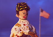 Image of a woman scarecrow with hair rollers and robe alongside road with American flag in background, Lancaster, Pennsylvania
