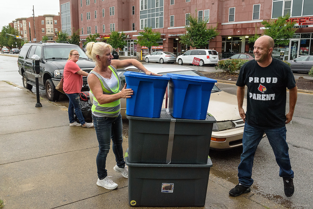 Freshman Mikayla Downs, 18, left, watches her parents Evelyn and Doug Downs load her stuff for the move from their parking space on Cardinal Boulevard to University Tower Apartments as first-time students move in to Belknap Campus dormitories Wednesday during University of Louisville's Welcome Week. Aug. 17, 2016