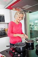 Smiling senior woman preparing food at kitchen counter