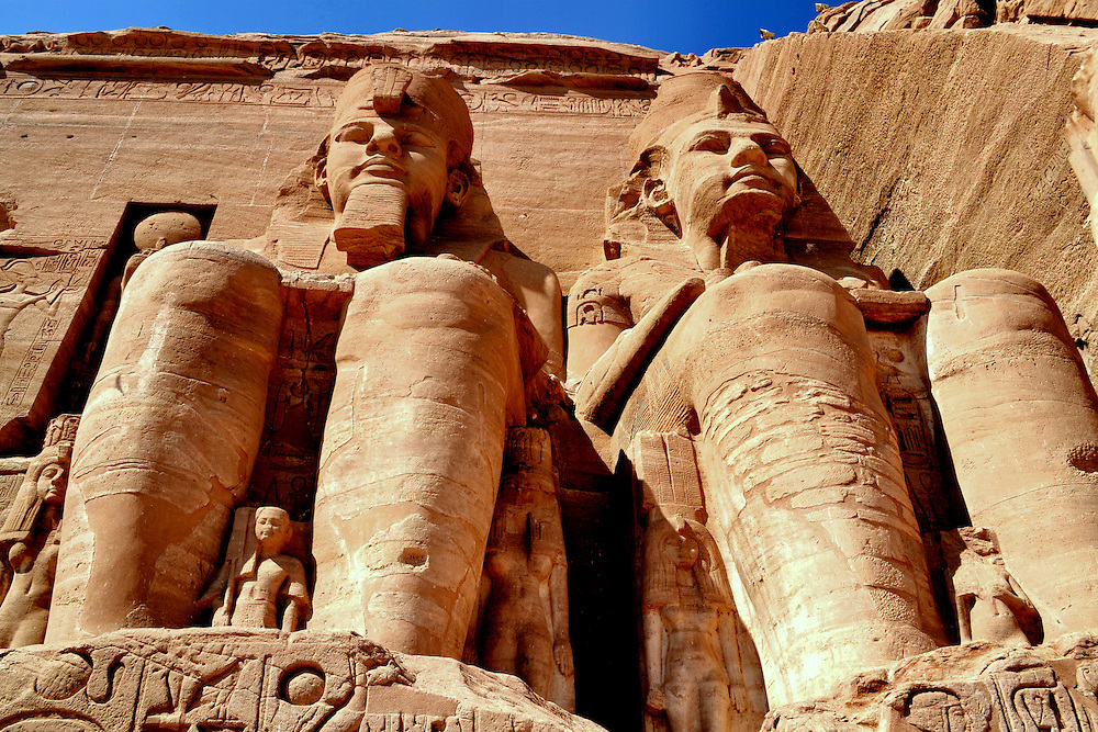 Giant Statues of Pharaoh Ramesses II at Temple of Ramesses in Abu Simbel, Egypt<br /> In the Nubian Desert in southern Egypt is the Temple of Ramesses in Abu Simbel. Outside are four mammoth images of the pharaoh. They were carved out of a mountain in 1244 BC. Nearby are two smaller temples. One is dedicated to Hathor, the goddess of motherhood. The other honors Queen Nefertari, the wife of Ramesses the Great. When these sites were threatened to go underwater from Lake Nasser, $40 million was spent over four years to dismantle and reassemble them 650 feet away.