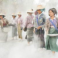 Women in Myanmar build a road by hand. Rocks are gathered in baskets, poured on the ground, and flattened with a steam roller.