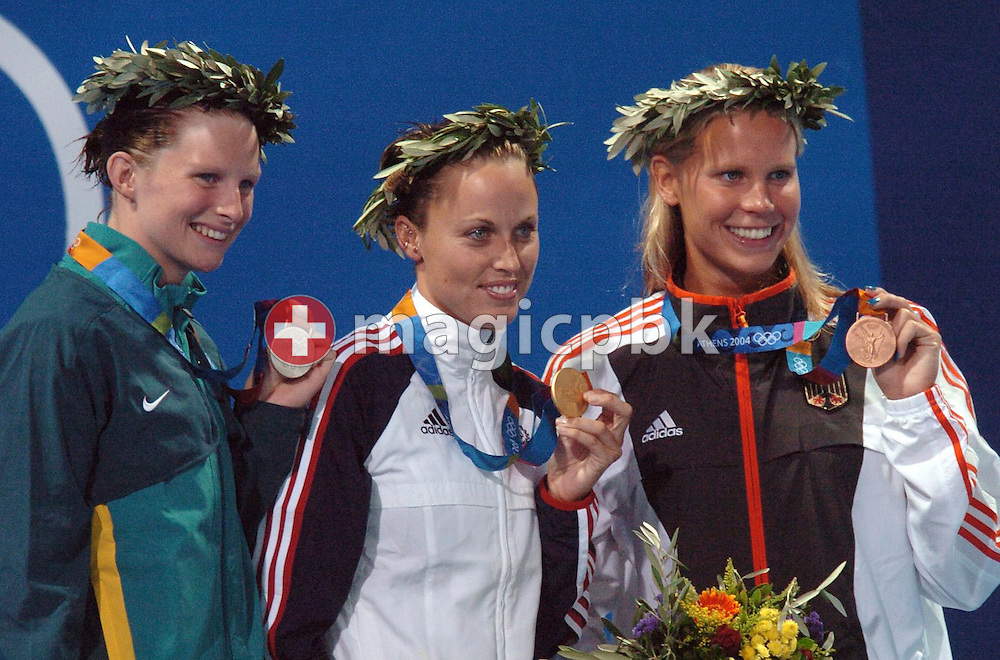 Amanda Beard from the USA (C) shows off the gold medal she won in the women's 200m Breaststroke final next to silver medalist Leisel Jones from Australia (L) and bronze medalist Anne Poleska from Germany at the Athens Olympic Aquatic Centre, Thursday, 19 August 2004.      (Photo by Patrick B. Kraemer / MAGICPBK)