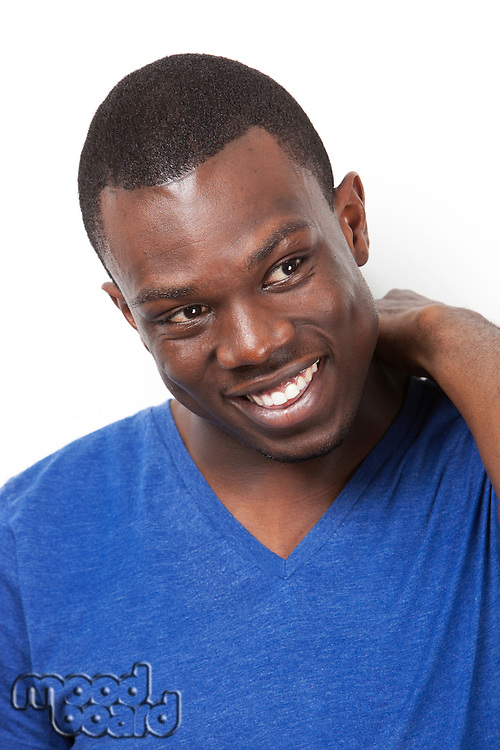 Happy young African American man looking away against white background