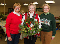 Opechee Garden Club's Barbara Sargent, Andris Clark and Marge Dyer get ready to pack up about 90 floral arrangements and this centerpiece (held by Clark) for a special delivery to the Belknap County Nursing Home Tuesday afternoon.  (Karen Bobotas/for the Laconia Daily Sun)