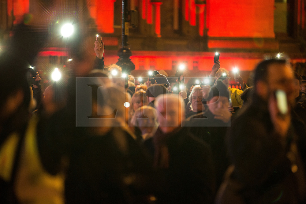 """© Licensed to London News Pictures . 03/02/2015 . Manchester , UK . People in the crowd raise their phones with the lights on , as part of the campaign , at the demonstration . Demonstration organised by the Labour Party on the steps of Manchester City Council in Albert Sqaure , Manchester , under the banner """"manVcam"""" ( Manchester vs Cameron ) . Organisers say Manchester - along with Liverpool and Birmingham - have suffered larger cuts than other regional authorities , whilst southern regions such as Surrey , Hampshire and West Sussex have all seen increases in government funding . Photo credit : Joel Goodman/LNP"""