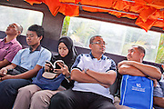 Sleeping, reading, watching. Bruneian Commuters take the water taxi through the mangrove swamps from Bangar to Bandar