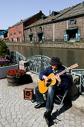Busker playing guitar beside canal in historic Otaru on Hokkaido island in Japan