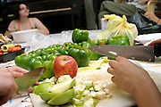 Members of the Freegan community in New York cutting apples and peppers at a dinner cooked entirely with food recovered from dumping sites around the island of Manhattan, New York, NY., on Friday, June 23, 2006. Freegans are a community of people who aims at recovering wasted food, books, clothing, office supplies and other items from the refuse of retail stores, frequently discarded in brand new condition. They recover goods not for profit, but to serve their own immediate needs and to share freely with others. According to a study by a USDA-commissioned study by Dr. Timothy Jones at the University of Arizona, half of all food in the United States is wasted at a cost of $100 billion dollars every year. Yet 4.4 million people in the United States alone are classified by the USDA as hungry. Global estimates place the annual rate of starvation deaths at well over 8 million. The massive waste generated in the process fills landfills and consumes land as new landfills are built. This waste stream also pollutes the environment, damages public health as landfills chemicals leak into the ground, and incinerators spew heavy metals back into the atmosphere. Freegans practice strategies for everyday living based on sharing resources, minimizing the detrimental impact of our consumption, and reducing and recovering waste and independence from the profit-driven economy. They are dismayed by the social and ecological costs of an economic model where only profit is valued, at the expense of the environment. In a society that worships competition and self-interest, Freegans advocate living ethical, free, and happy lives centred around community and the notion that a healthy society must function on interdependence. Freegans also believe that people have a right and responsibility to take back control of their time.