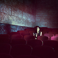 A young woman sitting in an empty cinema