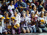 30 SEPTEMBER 2017 - BANGKOK, THAILAND:  People wait for the chariot carrying the deity during the Navratri parade in Bangkok. They were covered in colored powders thrown by Hindu priests. Navratri is a nine night (10 day) long Hindu celebration that marks the end of the monsoon and honors of the divine feminine Devi (Durga). The festival is celebrated differently in different parts of India, but the common theme is the battle and victory of Good over Evil based on a regionally famous epic or legend such as the Ramayana or the Devi Mahatmya. Navratri is celebrated throughout Southeast Asia in communities that have large Hindu population. Bangkok's celebration of Navratri was subdued this year because Thais are still mourning the death of Bhumibol Adulyadej, the Late King of Thailand, who died on October 13, 2016.     PHOTO BY JACK KURTZ