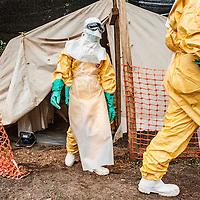 21/04/2014. Gueckedou. Guin&eacute;e Conakry.  <br /> <br /> Deux jours apr&egrave;s avoir &eacute;tait test&eacute;e positive &agrave; l'Ebola, Finda Marie Kamano d&eacute;c&egrave;de.<br /> <br /> Les sanitaires s'habillent pour pr&eacute;senter la d&eacute;funte &agrave; sa famille et leur assurer que c'est bien elle qui est dans le sac mortuaire herm&eacute;tique.<br /> <br /> Two days after was tested positive for Ebola, Finda Marie Kamano dies. <br /> <br /> The sanitary dress to present the defunct to her family and to assure them that it is she who is in the sealed body bag.<br /> &copy;Sylvain Cherkaoui/Cosmos/MSF