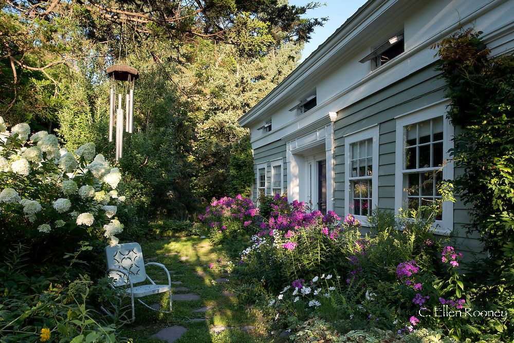Wind chimes, vintage furniture, Phlox, Hydrangea and Cosmos in artist, Katherine Bowling's cottage garden in Potter Hollow, New York State, U.S.A.