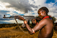 Hamer tribe man holding an AK-47 assault rifle, Omo Valley, Ethiopia.