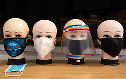Edinburgh, Scotland, UK. 24 July, 2020. Row of mannequin heads display range of face coverings for sale in shop. Iain Masterton/Alamy Live News