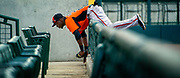 Orioles right fielder Trayvon Robinson (25) teeters on the fence after chasing a foul ball into the stands of Ed Smith Stadium at the team's spring training facility in Sarasota, Fla. Robinson failed to make the play, stopped by the fence.