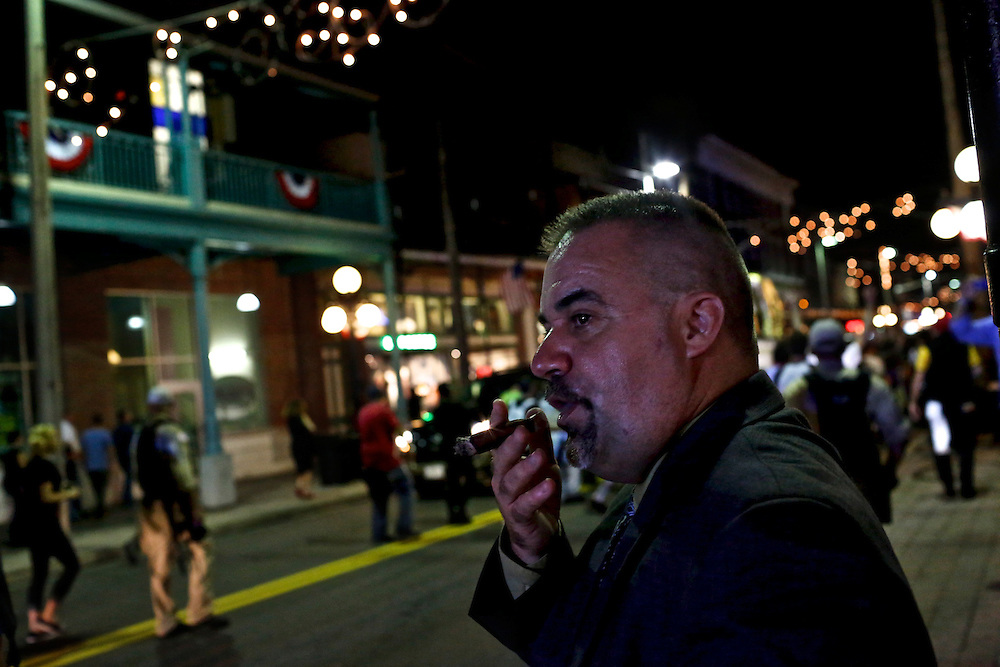 A patron of Ybor City businesses smokes a cigar while watching anti-GOP demonstrators participate in a dance party flash mob through the streets of Ybor City during the 2012 Republican National Convention in Tampa, Fla.