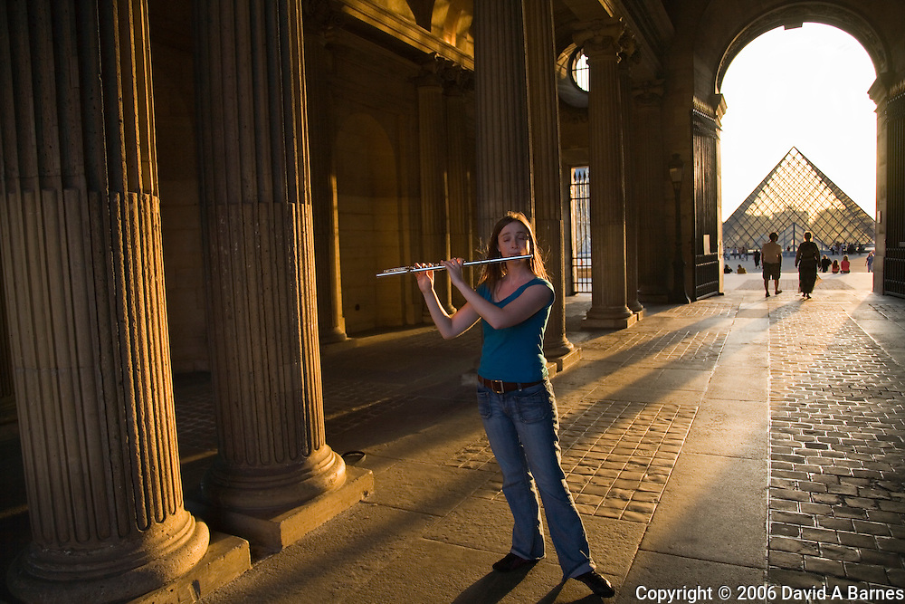 Street musicain playing flute in passageway of Louvre, Paris, France