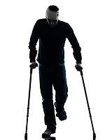 one injured man walking with crutches in silhouette studio on white background
