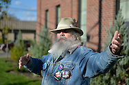 "Merrick, New York, USA. October 23, 2016. FRED S. CHANDLER, 66, of North Bellmore, wearing several political campaign buttons supporting Democratic presidential candidate Hillary Clinton, gestures with hand while talking during rally to demand public water and stop New York American Water (NYAW) rate hike. On denim jacket were buttons for Hofstra University DEBATE 2016 - and ""So My Daughter Knows She Can Be President. Hillary 16"" - ""TRUMPBUSTERS"" - ""CLINTON KAINE 16"" - and Monopoly Man character with ""NEVER TRUMP"" text."