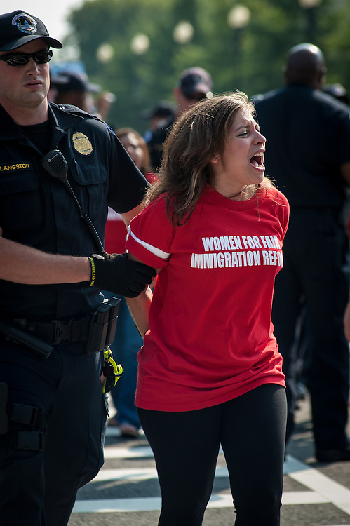 WASHINGTON, DC -- 9/12/13 -- A woman continues chanting slogans after being handcuffed….  Approximately 100 women staged a rally then blocked the intersection at New Jersey and Independence Avenues in front of the Capitol to demand action on comprehensive immigration reform. ..…by André Chung #AC2_0736