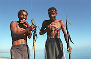 Fishermen with their spears from the morning dive in Dili beaches.  @ Martine Perret. 2003