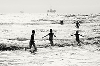 Playing in the surf  with oil rigs in the background in Huntington Beach, California.