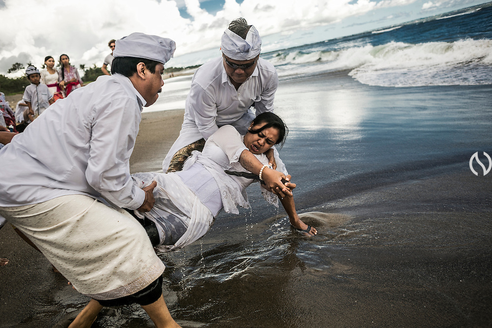 "BALI, INDONESIA; MARCH 17, 2015: A Balinese Hindu devotee possesed by spirit and stab herself using ""Keris"", Balinese sword during Melasti, a cleansing ritual before entering Silent Day i Batubolong beach, Bali, Indonesia on Tuesday, March 17, 2015."