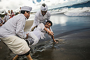 """BALI, INDONESIA; MARCH 17, 2015: A Balinese Hindu devotee possesed by spirit and stab herself using """"Keris"""", Balinese sword during Melasti, a cleansing ritual before entering Silent Day i Batubolong beach, Bali, Indonesia on Tuesday, March 17, 2015."""