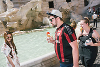 """ROME, ITALY - 20 JUNE 2017: Tourists eating ice cream by the Trevi Fountain walk away after being warned by a policewoman entrusted to protect the fountain, in Rome, Italy, on June 20th 2017.<br /> <br /> The warm weather has brought a menacing whiff of tourists behaving badly in Rome. On April 12, a man went skinny-dipping in the Trevi fountain resulting in a viral web video and a 500 euro fine.<br /> <br /> Virginia Raggi, the mayor of Rome and a national figurehead of the anti-establishment Five Star Movement,  issued an ordinance involving harsher fines for eating, drinking or sitting on the fountains, for washing animals or clothes in the fountain water or for throwing anything other than coins into the water of the Trevi Fountain, Bernini's Four Fountains and 35 other city fountains of artistic or historic significance around the city.  """"It is unacceptable that someone use them to go swimming or clean themselves, it's an historic patrimony that we must safeguard,"""" Ms. Raggi said."""
