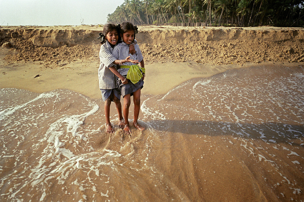 Vijyashree Viswanathan (age 7, left), and sister Vijitha (age 9, right) stand on the shore close to the point where Vijitha and Vijashree's mother and brother lost their lives. This is the first occasion since the tsunami, that Vijitha and Vijyashree have ventured close to the sea.<br /><br />These photographs encompass four years in the lives of two families of children from South India who lost their mothers to the Asian tsunami. Following that momentous event in 2004, the five Krishnamurthy sisters from Puddupettai went to live in the Cuddalore Government Special Home for Tsunami Children. And Vijitha and Vijyashree Viswanathan, after an initial brief spell at the same home, now live with their father and his new wife in the nearby fishing village of Thalanguda. <br /><br />Each child affected by the tsunami had to adapt to changed circumstances and cope with emotions no one in their family could have possibly anticipated. The younger children seemed to adjust more quickly than their older siblings. And, while grief rendered some silent, in others it provoked a real sense of anger. Some became withdrawn while others craved attention and resorted to disruptive behavior. For all of the children, the experience of losing a parent seemed to strengthen the bond they shared with their brothers and sisters. <br /><br />The loss of a parent meant that some of the children photographed in this project inherited responsibilities that, while often a burden, provided a distraction from their own painful emotions. Sivaranjini Krishnamurthy lost her mother to the tsunami and then, together with her four younger sisters was abandoned by her father. At eleven years of age she took on the role of a mother to her younger sisters. Though she attends school and receives the support of orphanage staff, Sivaranjini has sacrificed much of her own childhood to take care of them. <br /><br />For Sivaranjini and the other children whose experiences are presented here, the tsunami is a def