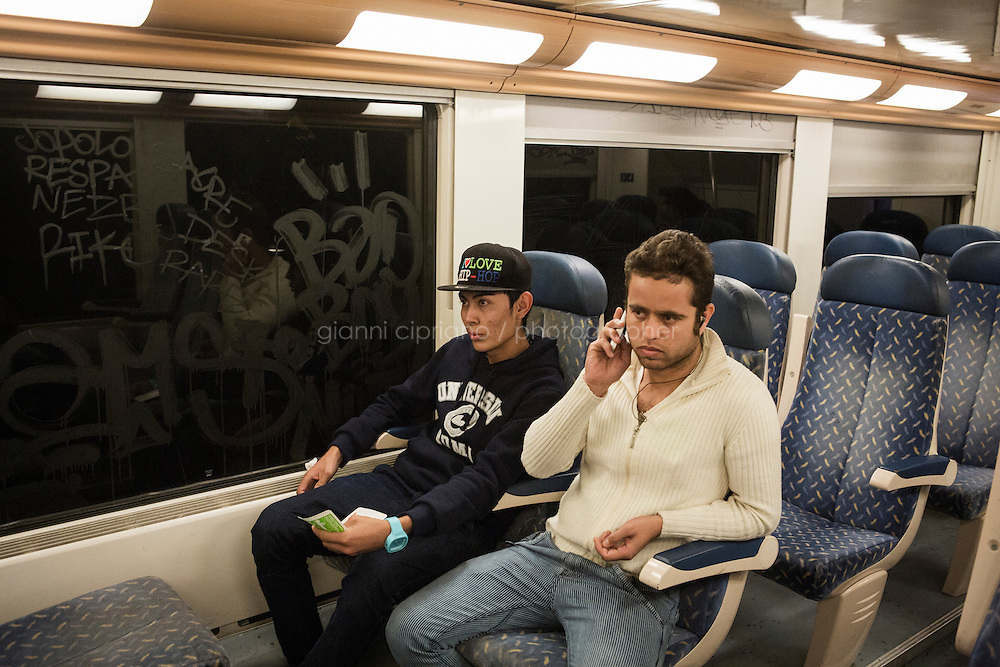 BEAUSOLEIL, FRANCE - 17 NOVEMBER 2014: (R-L) Afghan refugees Ajmir (25) and Ali (18) take the train that goes from Ventimiglia to Nice, taken by migrants that want to cross the border from Italy to France, in Beausoleil, France, on November 17th 2014. They are trying to call their friend that was caught by the French border patrol in Menton that pushed him back to Italy. <br /> <br /> The Ventimiglia-Menton border is the border between Italy and France crossed by migrants who decide to continue their journey up north towards countries such as Germany, Sweden, The Netherlands and the UK where the process to receive the refugee status or humanitarian protection is smoother and faster. in Ventimiglia, Italy, on November 17th 2014.